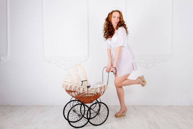 Beautiful young pregnant woman teenager in white dress with baby carriage
