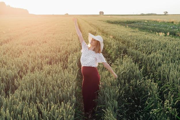 들판을 걷는 동안 아름다운 젊은 임산부는 손을 흔들며 나가는 태양에 작별을 고합니다. 임신 관리. 아름다움과 건강. 행복과 평온. 건강한 생활.