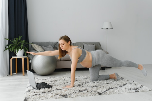 Beautiful young pregnant woman with laptop training at home