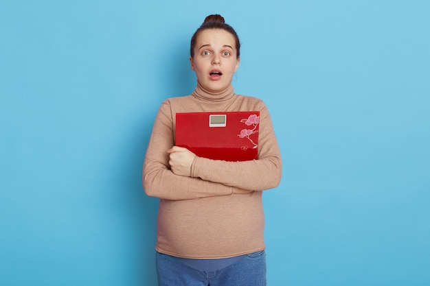 Beautiful young pregnant woman with shocked facial expression and mouth opened, holding a red scale in hands