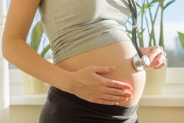 Красивая молодая беременная женщина с стетоскопом