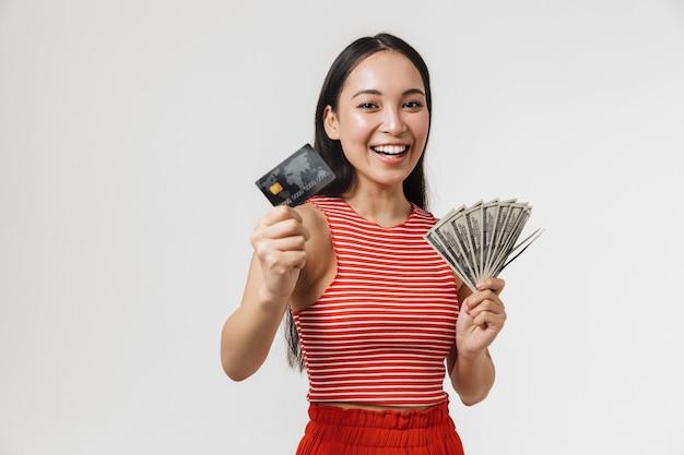 신용 카드와 돈을 들고 흰 벽 위에 고립 된 포즈를 취하는 아름다운 젊고 예쁜 아시아 흥분한 여성.
