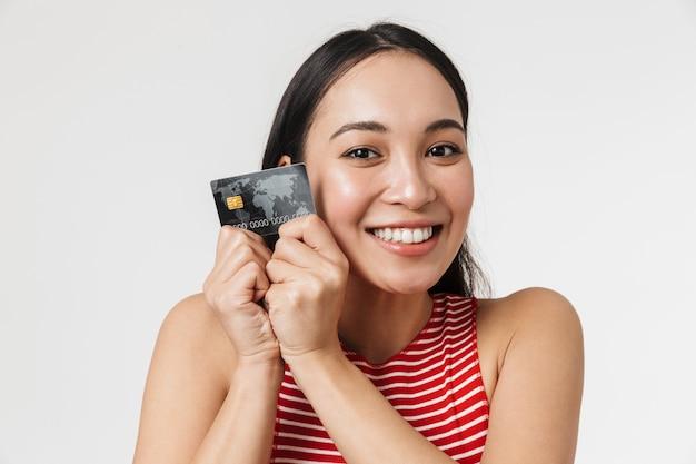 아름 다운 젊은 꽤 아시아 흥분된 여자 신용 카드를 들고 흰 벽에 고립 된 포즈.