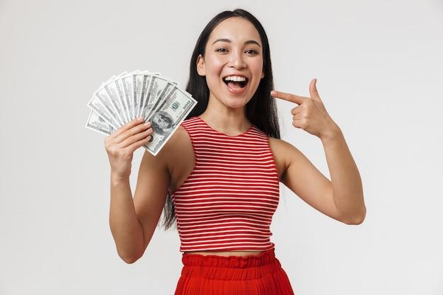 아름 다운 젊은 예쁜 아시아 여자 돈을 들고 흰 벽 위에 고립 된 포즈.