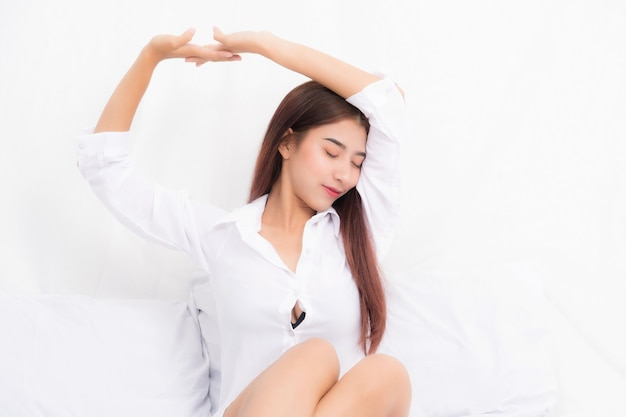 Красивая молодая довольно азиатская женщина просыпается и растягивается с белой рубашкой на белой кровати утром.