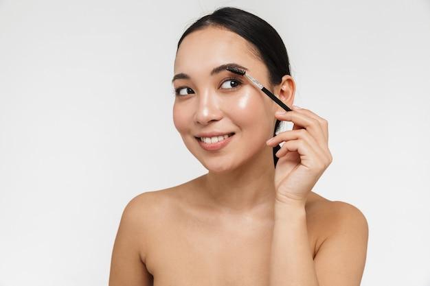 Красивая молодая довольно азиатская женщина со здоровой кожей позирует обнаженной, изолированной над белой стеной, держащей стайлер бровей. Premium Фотографии