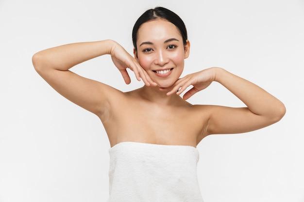 하얀 벽 위에 벌거벗은 채 포즈를 취하는 건강한 피부를 가진 아름다운 젊고 예쁜 아시아 여성.