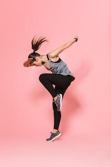 走っている美しい若いかなりフィットネスの女性は、ピンクの壁に隔離されたスポーツエクササイズを作ります Premium写真