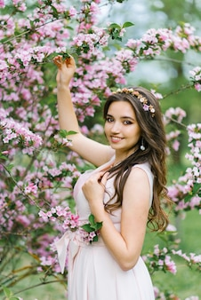 A beautiful young pretty girl with long hair loose stands near the blooming spring bush of weigela with pink flowers. she touches a branch with her hand. professional makeup
