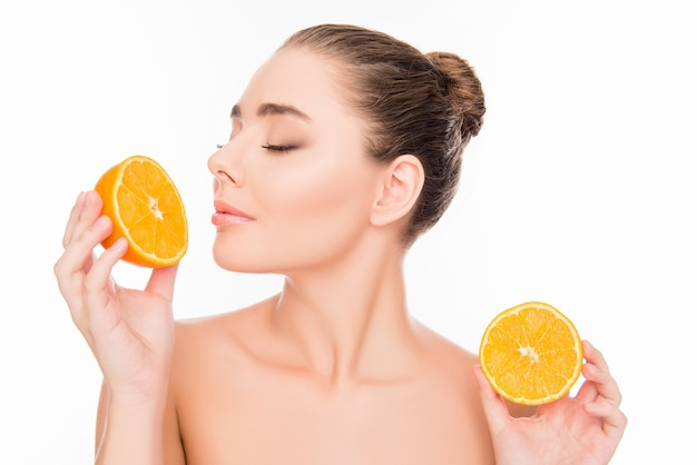 Beautiful young pretty woman holding two halves of orange and smelling it