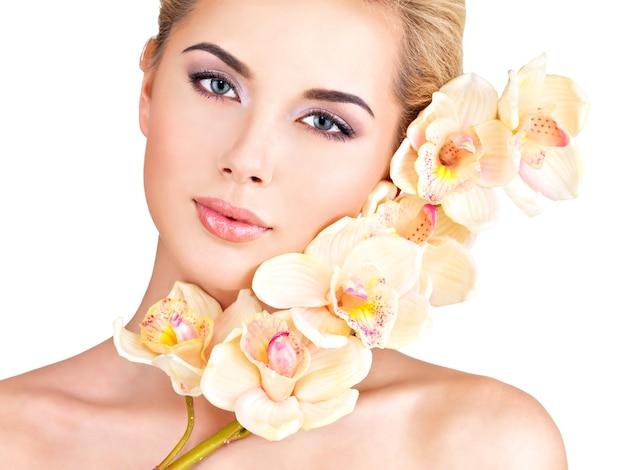 Красивая молодая красивая женщина со здоровой кожей и цветами рядом с лицом - изолированные на белом