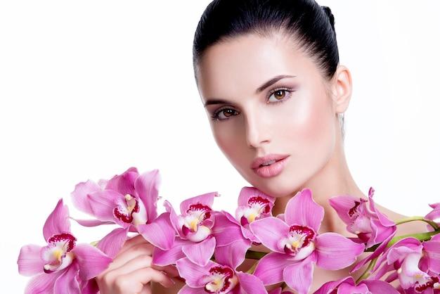 건강 한 피부와 얼굴에 가까운 꽃 아름 다운 젊은 예쁜 여자-흰색 절연.