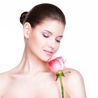 Beautiful young pretty woman with healthy skin and pink rose near face - isolated on white.