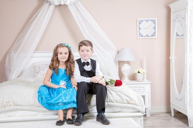 턱시도 정장을 입은 아름다운 어린 왕자와 파란 드레스를 입은 장미를 들고 있는 공주와 밝은 방에 있는 침대에 앉아 먼 곳을 바라보는 패션 밴드가 포즈를 취하고 있습니다. 사랑 이야기. 스튜디오 촬영.