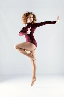 白い背景の上で踊っている、美しい若いプロのダンサー。
