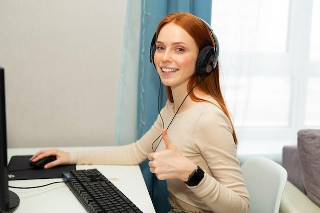 Красивая молодая рыжая женщина за столом с компьютером в наушниках с жестом руки