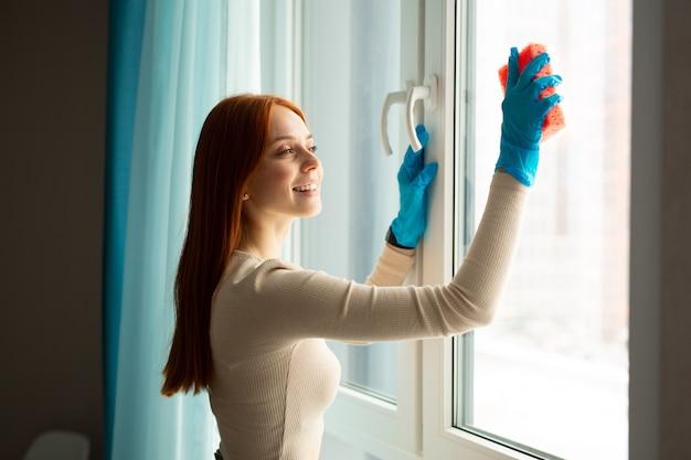 Красивая молодая рыжая женщина убирает дом