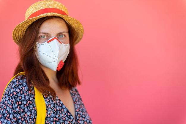 防護マスクの帽子と夏のドレスで美しい赤い髪の少女が通りのピンクの壁の近くに立っている防護マスク