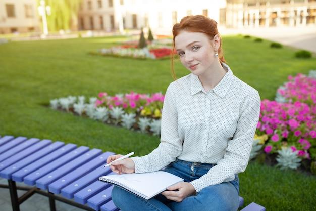 Красивая молодая рыжеволосая девушка с веснушками сидит на скамейке