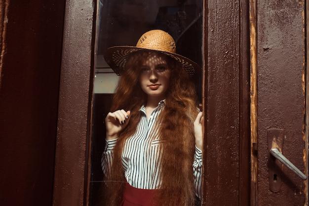 彼女の顔とそばかすに影のある麦わら帽子の美しい若い赤い髪のモデル