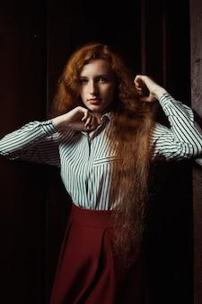 흰색 줄무늬 셔츠와 빨간 치마를 입은 아름다운 젊은 빨간 머리 모델. 어두운 방에서 포즈를 취하는 여자