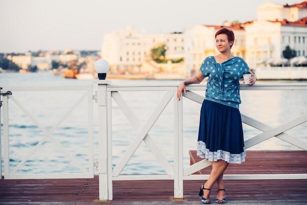Красивая молодая рыжеволосая улыбающаяся девушка с короткими волосами на пристани в джинсовой блузке и открытом портрете юбки.