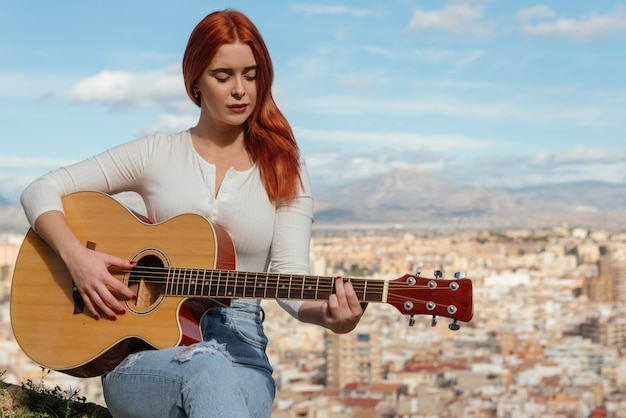 Beautiful young redhaired girl plays the guitar outdoors