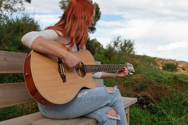 Красивая молодая рыжеволосая девушка играет на гитаре на открытом воздухе