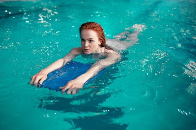 Красивая молодая рыжая девушка кавказа плавает в крытом бассейне. здоровый образ жизни.