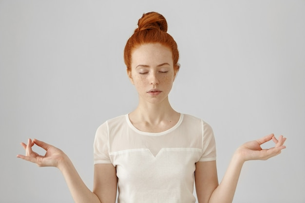 Beautiful young redhead female doing yoga in the morning indoors at white wall