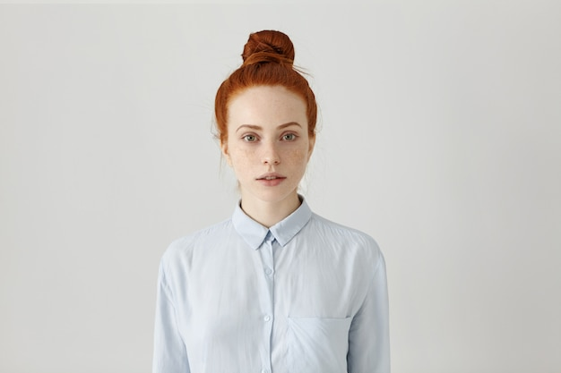 Beautiful young redhead female employee with hair bun posing indoors dressed in light blue formal shirt, getting prepared for work, having serious look. horizontal, isolated shot