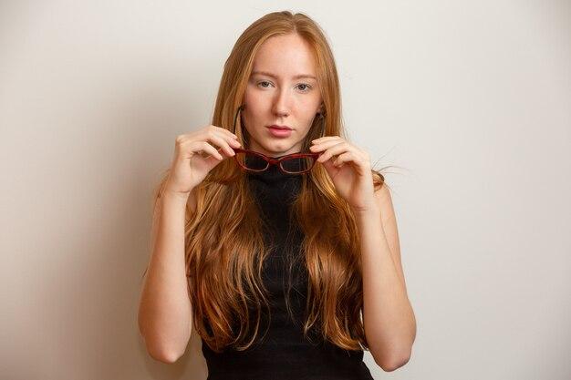 眼鏡の美しい若い赤毛の女の子は、灰色の背景に笑みを浮かべてです。