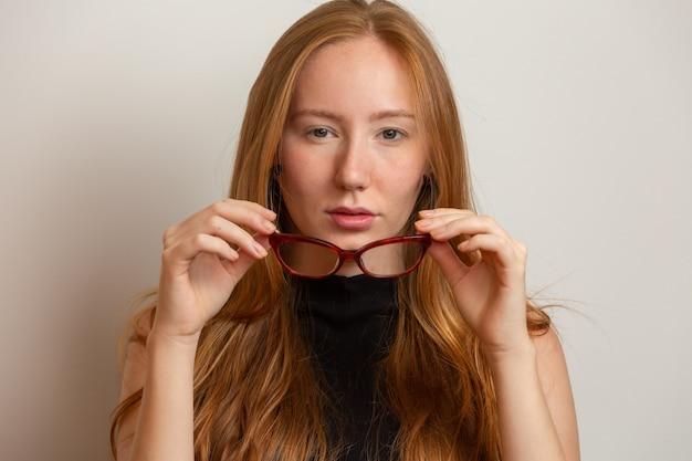 眼鏡の美しい若い赤毛の女の子は、灰色の壁に、笑みを浮かべて