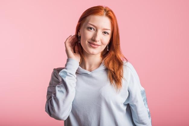 ピンクの背景にスタジオで美しい若い赤毛の女の子