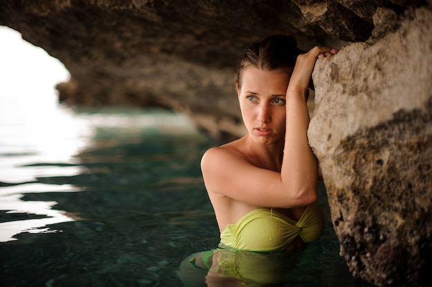 Beautiful young redhead girl with grey eyes in the water cave