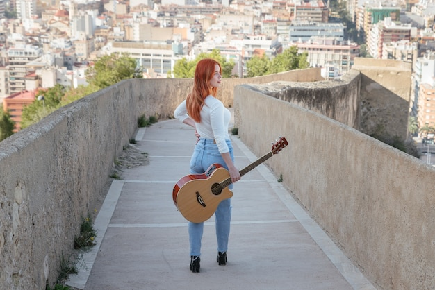 Beautiful young redhead walks with her guitar outdoors along a wall that has panoramic views of the city