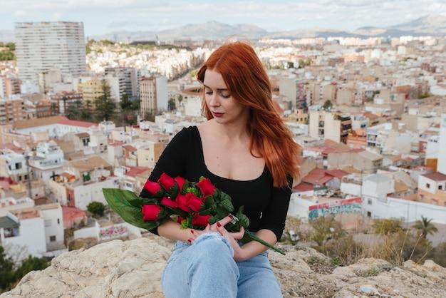 恋をしている美しい若い赤毛の女性は、彼女の腕の中で赤いバラを優しく見ています。バレンタイン・デー