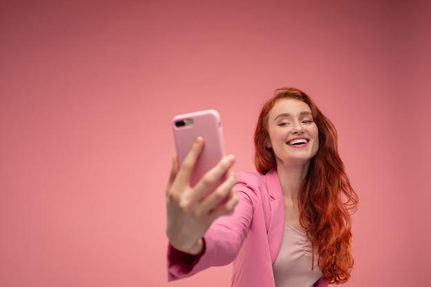 아름 다운 젊은 빨간 머리 여자 만들기 selfie