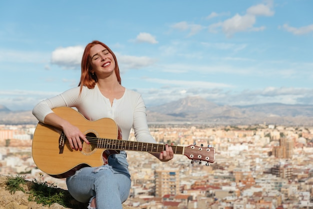 Beautiful young redhead woman plays guitar outdoors sitting on a a wall stone bench