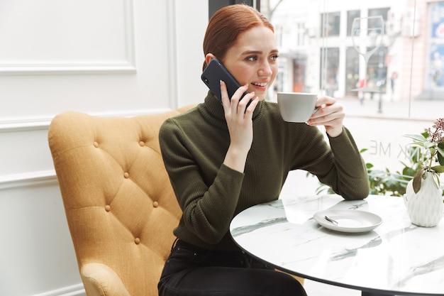 Красивая молодая рыжая женщина расслабляется за столом в кафе в помещении, пьет кофе, разговаривает по мобильному телефону