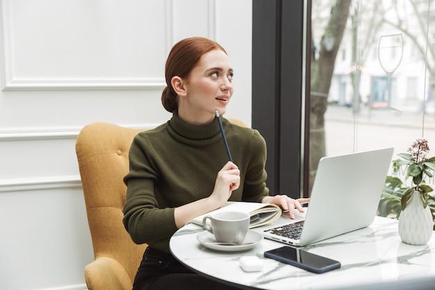 Красивая молодая рыжая женщина расслабляется за столом в кафе в помещении, пьет кофе, работает на портативном компьютере