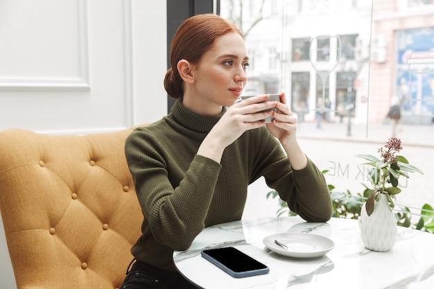 Красивая молодая рыжая женщина расслабляется за столом в кафе в помещении, пьет кофе