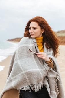 Красивая молодая рыжеволосая женщина в пальто, покрытом одеялом, гуляет на пляже