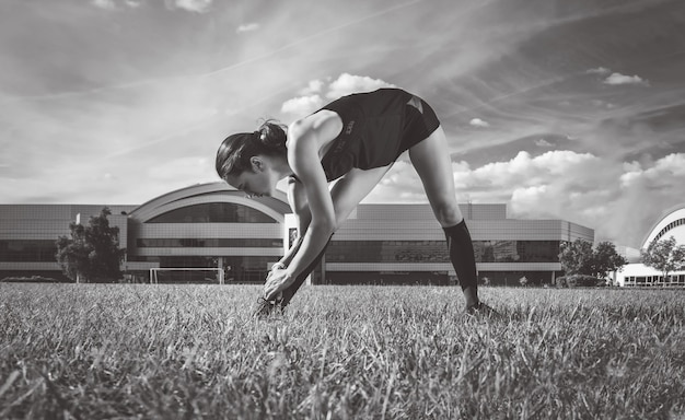 Красивый молодой бегун разминается на футбольном поле перед гонкой. спортивная концепция.