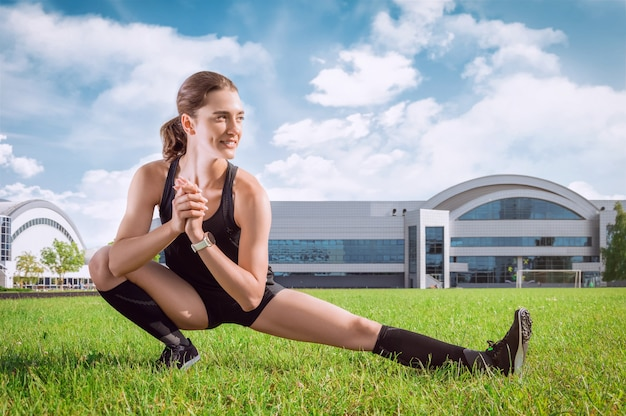 Beautiful young runner warms up on the soccer field before the race. sports concept.