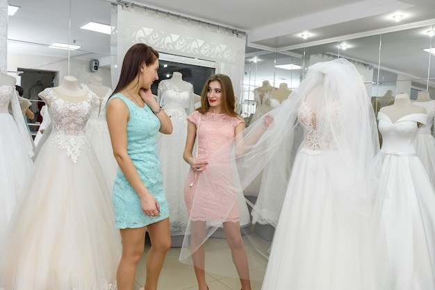 Beautiful young sales woman showing wedding dress to a customer