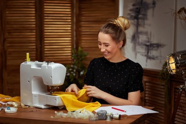 Красивая молодая швея работает на швейной машине