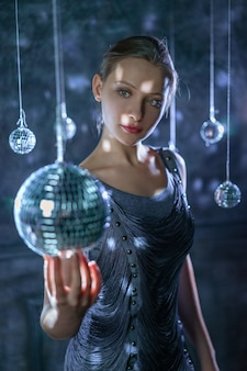 Beautiful young sensual woman holding disco ball