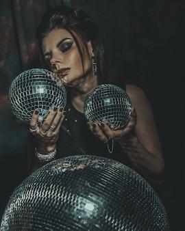 Beautiful young sensual woman holding disco balls