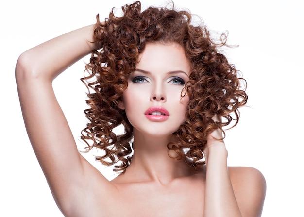 Bella giovane donna sensuale che tocca i suoi capelli a mano. bel viso con acconciatura riccia, isolato su bianco.